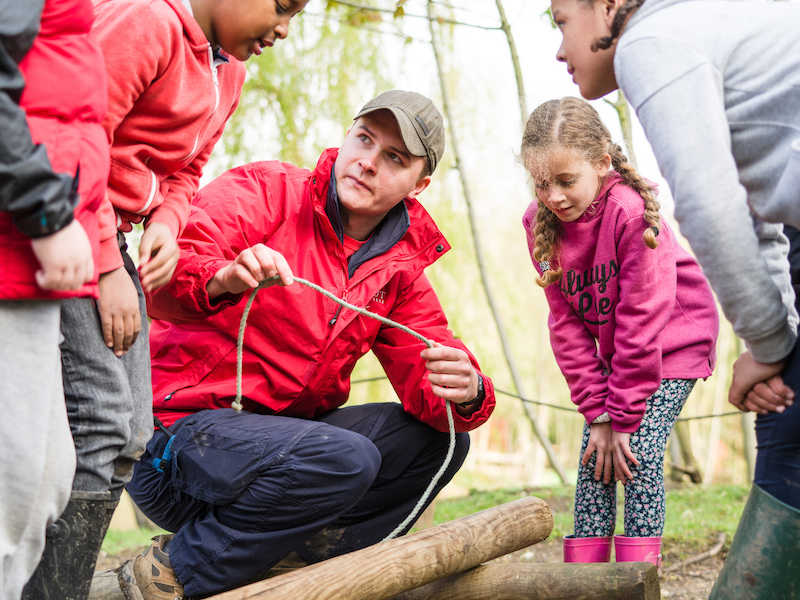 Scout Adventures volunteer teaching rope skills to young people