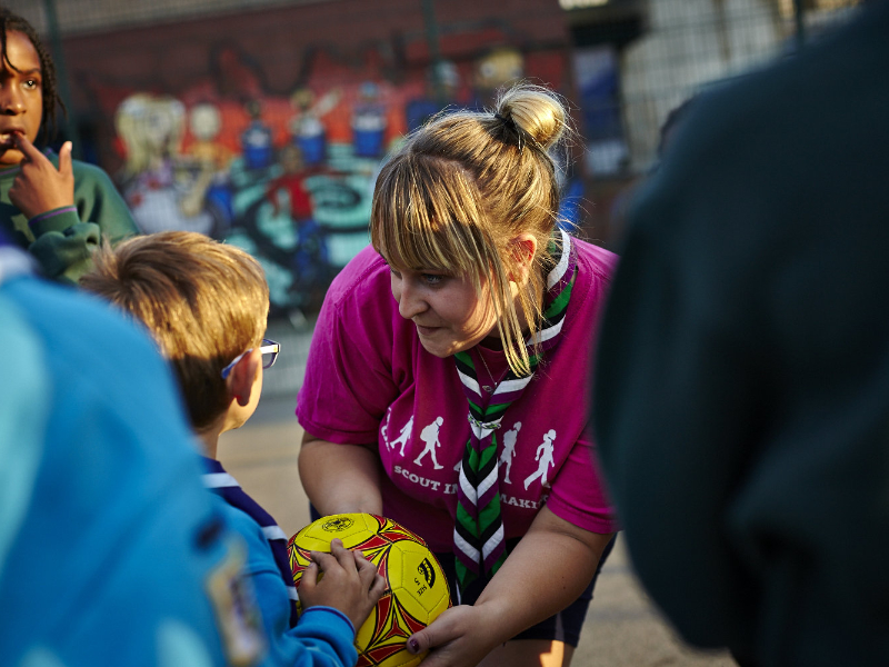 Volunteer encouraging Beavers and Cubs with an outdoor ball game