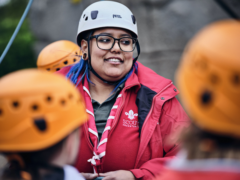 Scout Adventures volunteer explaining a climbing activity to young people