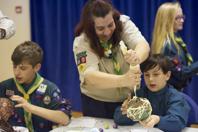 An adult volunteer helping a Scout with craft