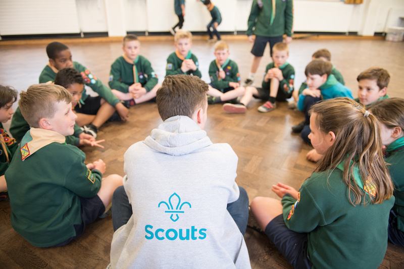 An adult volunteer sitting in a circle with Cub Scouts