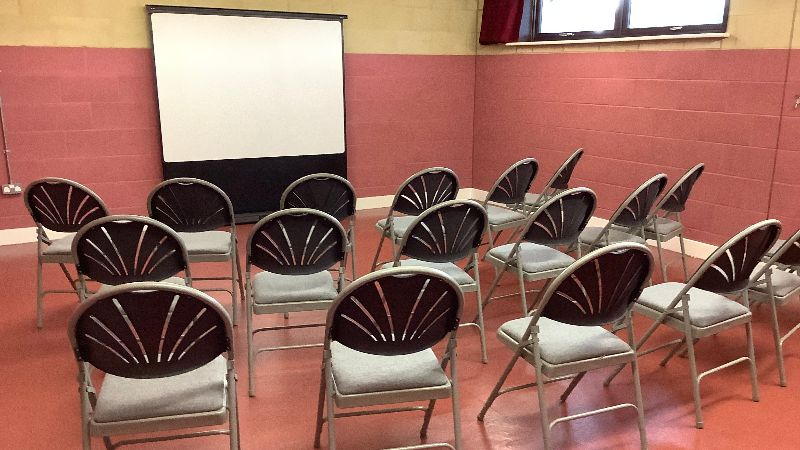 Our small hall set out with chairs & projector screen for a presentation