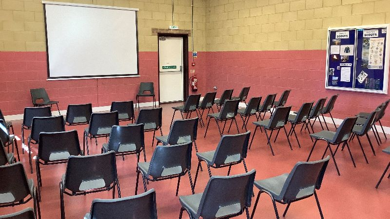 The Brian Spray hall set out with chairs & projector screen, presentation / lecture style